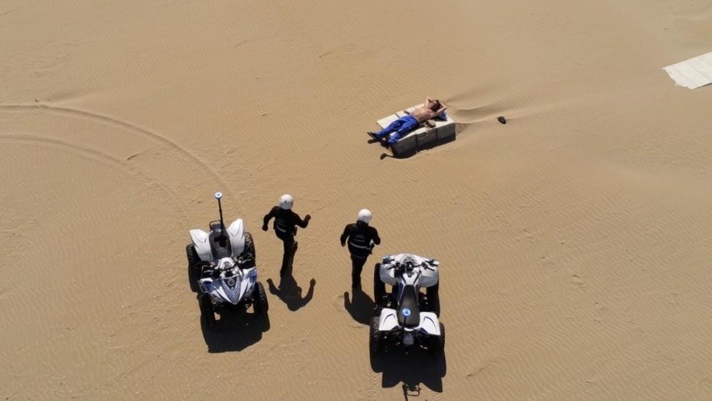 Drones captan cómo policías detienen a un hombre que toma el sol en una playa vacía en Italia, y la grabación provoca críticas en las redes